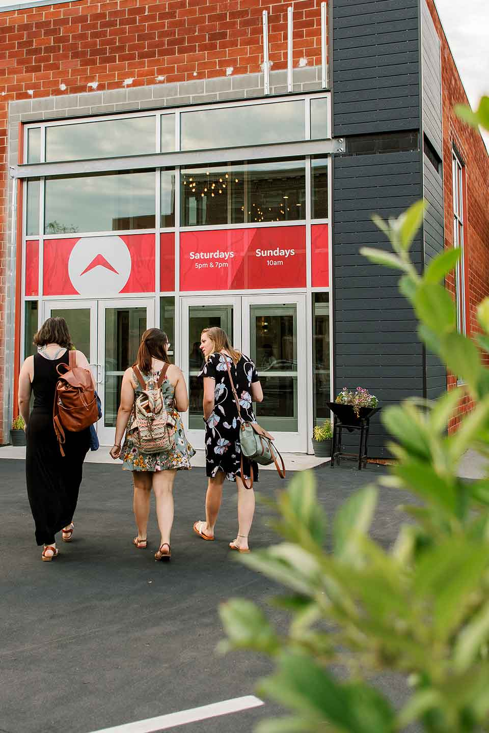 Three women approach the main entrance of Walnut Creek Church - Downtown